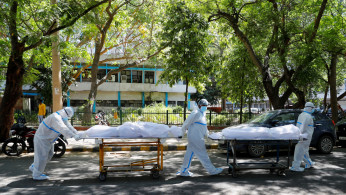 Health workers wearing personal protective equipment (PPE) carry bodies of people who were suffering from the coronavirus disease (COVID-19), outside the Guru Teg Bahadur hospital, in New Delhi, India, April 24, 2021.