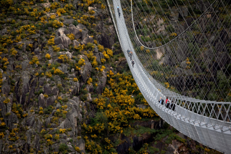 People walk on the world's longest pedestrian suspension bridge '516 Arouca', now open for local residents in Arouca, Portugal