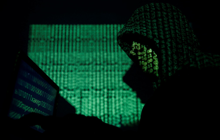 A hooded man holds a laptop computer as cyber code is projected on him in this illustration picture taken on May 13, 2017.
