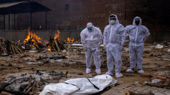 Men wearing protective suits stand next to the body of their relative, who died from the coronavirus disease (COVID-19), before her cremation at a crematorium ground in New Delhi, India, May 4, 2021.