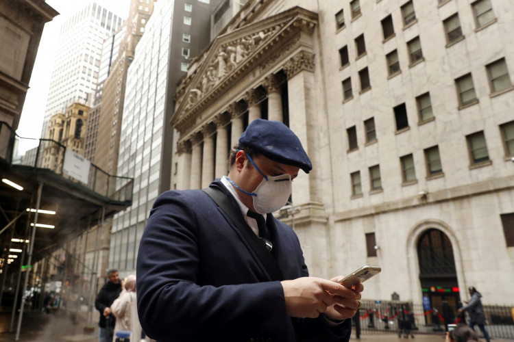 A man walks past the New York Stock Exchange on the corner of Wall and Broad streets in New York City.