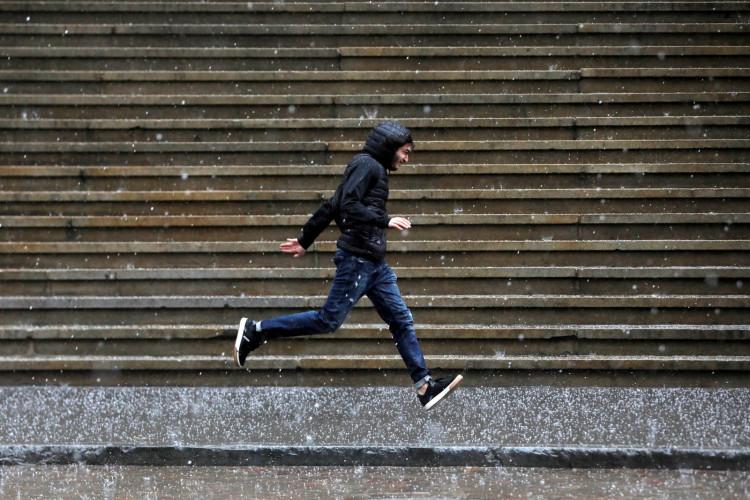A person runs along Wall Street as heavy rain and hail falls in New York City.