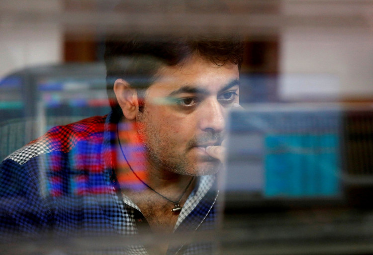 A broker reacts while trading at his computer terminal at a stock brokerage firm in Mumbai, India.