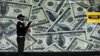 A security guard walks past a montage of old U.S. dollar bills outside a currency exchange.