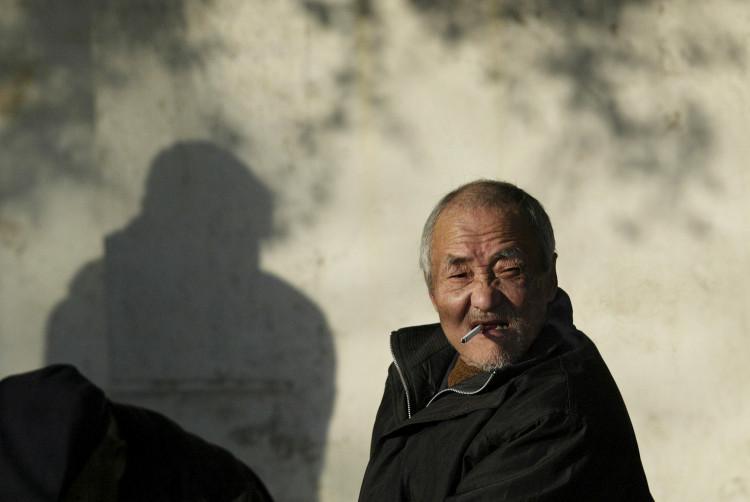 FILE PHOTO: An elderly man smokes on a street in Nanjing, Jiangsu province December 27, 2010.