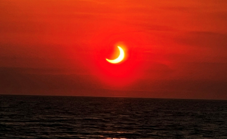 Partial solar eclipse is seen above the horizon in Avon-by-the-Sea