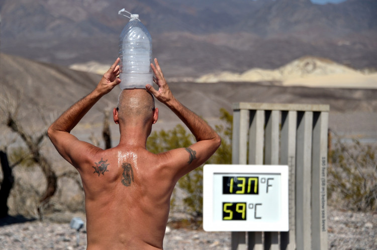 FILE PHOTO: Steve Krofchik of Las Vegas keeps cool with a bottle of ice on his head as the unofficial thermometer reads 130 degrees Fahrenheit