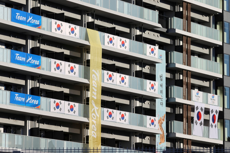 South Korean Flags and signs hang on the appartment building hosting Olympics participants at the Athletes Village