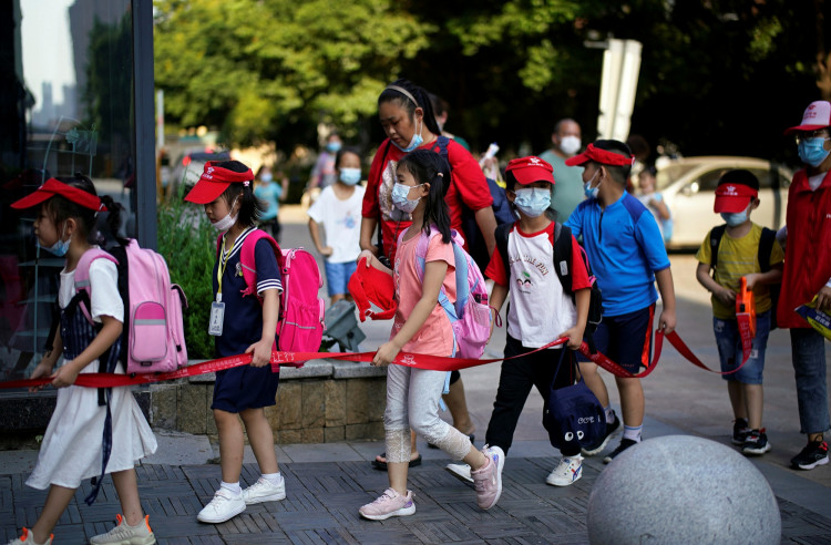 Students wearing protective face masks walk out of a primary school