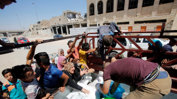 Citizens gather around a car that distribute meat for the poor families in the old city of Mosul