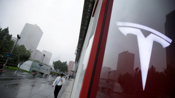 FILE PHOTO:  A man walks near a logo of Tesla outside its China headquarters at China Central Mall in Beijing, China July 11, 2018