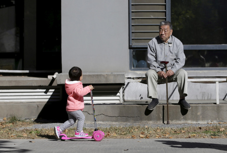 An 80-year-old man, surnamed Li, watches as a girl plays at a residential community in Beijing, China, October 30, 2015.