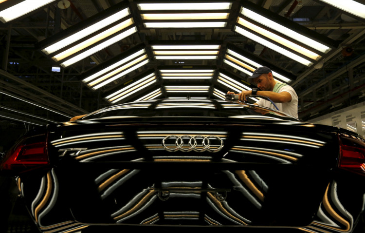 A worker stands next to a car on the assembly line as serial production of the new Audi TT roadster starts at the Audi plant in Gyor, west of Budapest