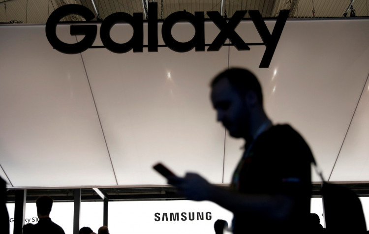 A visitor uses a mobile phone at the Samsung booth at the Mobile World Congress in Barcelona