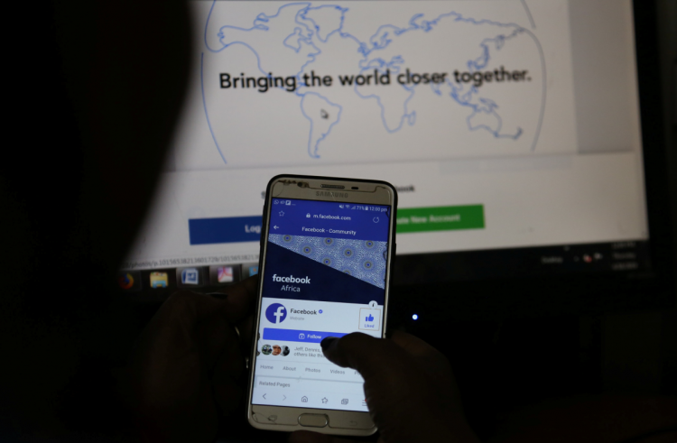 An illustration photo shows the Facebook page displayed on a mobile phone internet browser held in front of a computer screen